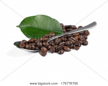 Pile of coffee grains with silver spoon and green leaf over white isolated background.