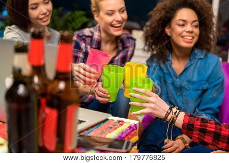 Side view of outgoing female friends clanging glasses together at party. They drinking beer. Happy concept