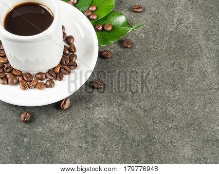 White cup filled with hot coffee roasted beans and green leaves scattered around the cup and dark gray granite for background captured from top view with sharp focus