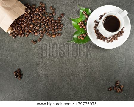 White cup filled with hot coffee roasted beans and green leaves scattered from paper bag. Dark gray granite for background captured from top view with sharp focus