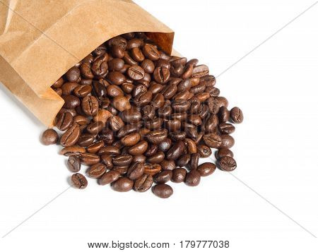 Scattered coffee grains from brown paper bag over isolated white background