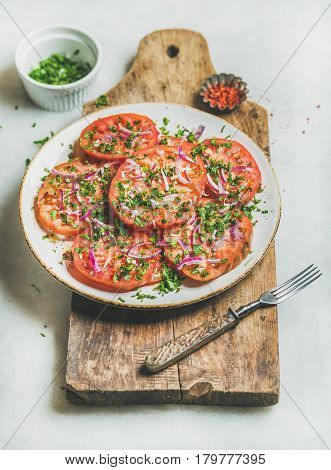 Fresh heirloom tomato, parsley and onion salad in white plate on rustic wooden board over light grey marble background, selective focus. Clean eating, vegan, vegetarian, healthy, dieting food concept
