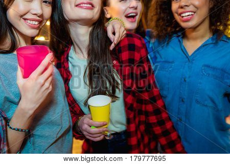 Outgoing young women standing near each other. They are drinking beer and laughing