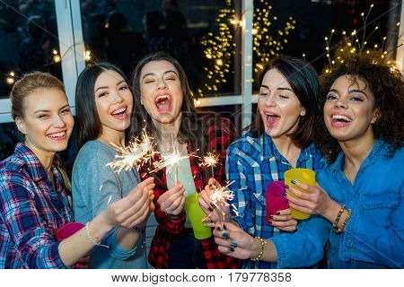 Asian, caucasian and african women having party with bengal light. They screaming and flourishing arms