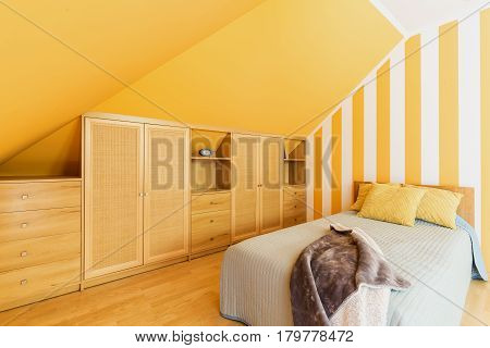 Attic Bedroom With Intense Yellow Walls