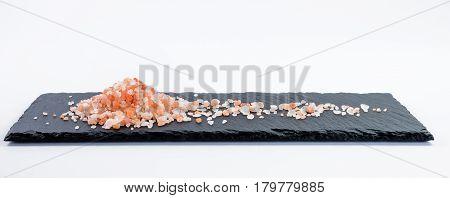 Handful of Hymalayan salt on dark shale plate on white background