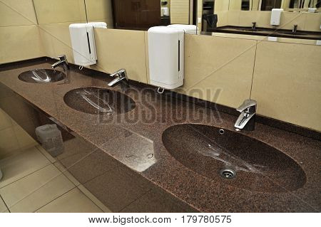three sinks in a   public restroom, interior