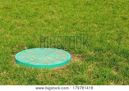 Green sewer hatch on the green grass in bright sunlight.