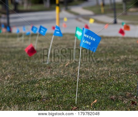 Utilities flag markers locating underground buried water, electric, gas and telephone lines. gas and telephone lines.