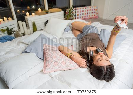 Calm young woman looking at mobile. She lying at mobile. Technology concept