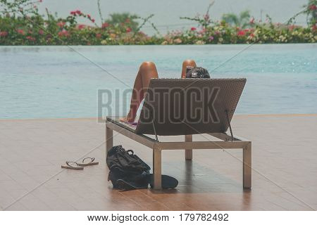 Relaxation Concept : Woman take a rest on daybed beside swimming pool and playing her smartphone.