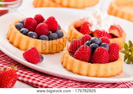 Tartlets with forest fruits on white dish.