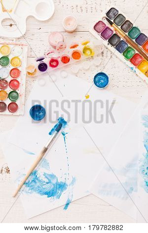 Top view on child's drawings and colorful paints and brushes. Creative ideas creativity andearly learning. Education concept.