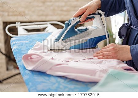 Housewife is ironing pink shirt. She standing at blue pressboard. Close up of her well-groomed hands