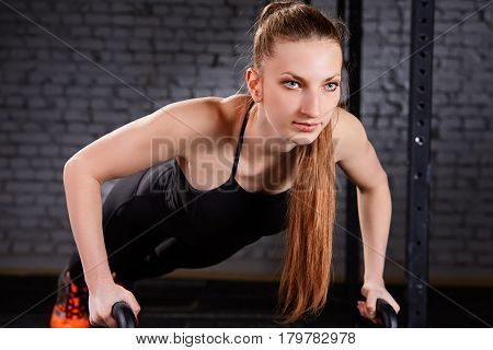 beautiful woman doing push ups on Kettlebells at crossfit gym against brick wall. Woman in the black sportwear, t-shirt and leggings. Healthy lifestyle. Crossfit concept.