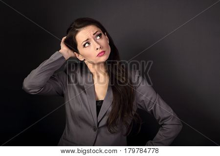 Serious Unhappy Business Woman In Suit Looking Up And Thinking On Dark Grey Background With Empty Co