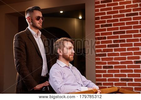 Photo of young handsome man who sitting in chair at barbershop with hairdresses who standing by the armchair. Hairdresser in the sunglasses. Completion of haircut. Master. Ctaftsmanship.