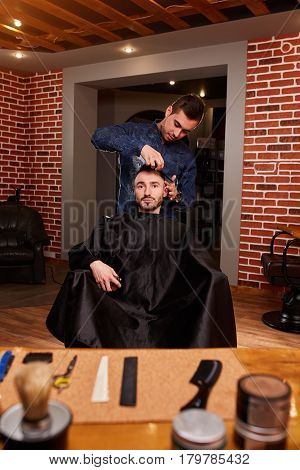 Hairdresser makes hairstyle for a young man with comb at the barbershop against brick wall. Vintage interior in the barbershop. Professionalizm and craftsmanship. Barbershop concept.