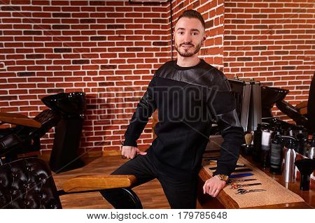 Young handsome hairdresse looking at camera while standing at barbershop and holds a scissors. Professionalizm and craftsmanship. Man in the black clothes. Horizontal portrait against brick wall.