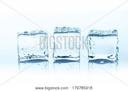 Group of three transparent ice cubes with reflection isolated on white background. Closeup of cold crystal block cutout