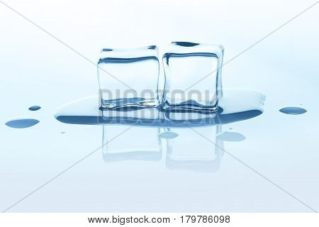 Group of melting ice cubes with reflection isolated on white background. Closeup of cold crystal block cutout