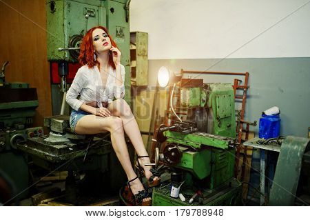 Red Haired Girl Wear On Short Denim Shorts And White Blouse Posed At Industrial Machine At The Facto