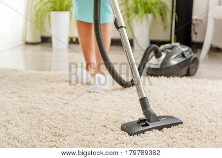 Housewife is making soft carpet clean with modern hoover. Focus on nozzle at rug. Close up of female legs