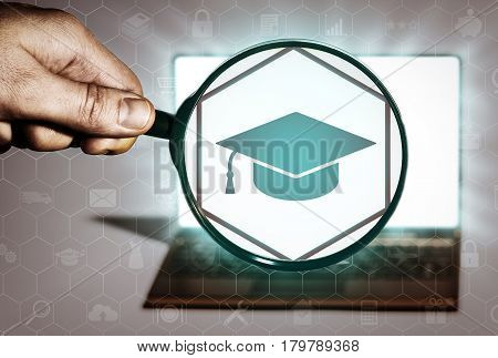 Hand holds the magnifying glass in front of an open notebook. Among the many icons attention is focused on the education icon. Search for courses educational institutions educational programs.