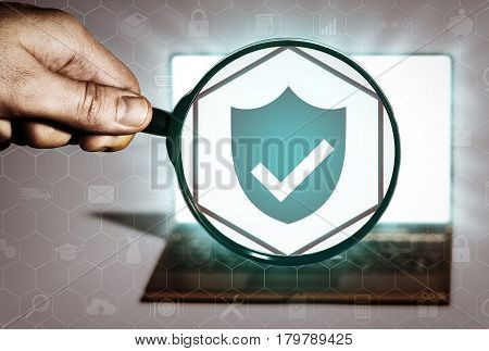 Hand holds the magnifying glass in front of an open notebook. Among the many icons attention is focused on the shield icon. Antivirus hacker protection.
