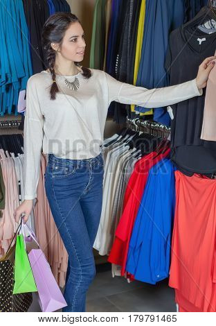 Beautiful girl chooses clothes at a shopping Mall with a bag of gifts. Smiling posing for the camera. To make purchases