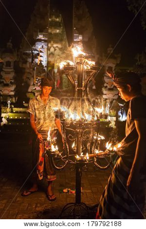Ubud, Indonesia - August 8, 2016: Unidentified balinese men light candles before a traditional Kecak Fire Dance ceremony in Hindu temple.