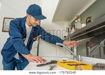 Attentive repairman is opening modern crane. He looking at running water with smile