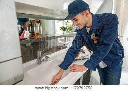 Cheerful repairman is working at modern sink. He standing in light kitchen