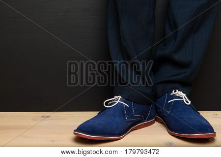 pair of male legs in blue shoes on the floor black background for an inscription