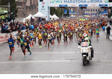 Rome Italy - April 2 2017: the departure of the athletes on Via dei Fori Imperiali the Coliseum on background. In the foreground the Senegalese and Moroccan athletes