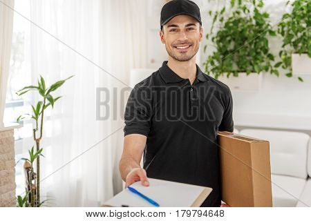 Smiling deliveryman is holding box and showing folder with pen. He looking at camera with smile. portrait