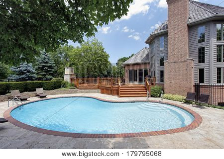 Swimming pool in back of luxury home with wood deck.