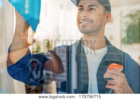 Smiling meticulous male person making window spotless with detersive spray and rag