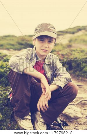 Portrait of a boy with a stern face during traveling in the mountains. Toned image.