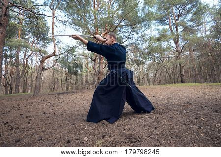 Concentrated man with a Japanese sword a katana practicing Iaido in a pine forest. Wide angle. Back view.
