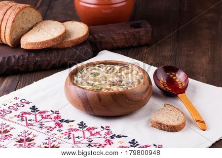 Traditional russian Cold Soup Okroshka with meat, vegetables and kvass serving size in wooden bowl and rye bread on wooden table. Kvass is a traditional Slavic and Baltic fermented beverage commonly made from rye bread