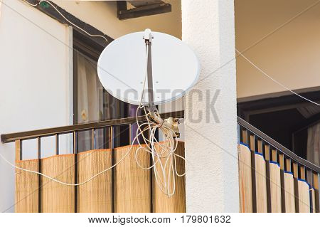 satellite dish and TV antennas on the house balcony.