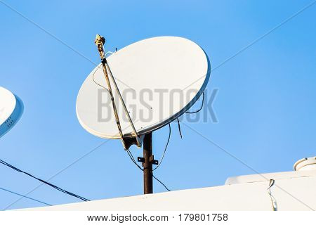 satellite dish and TV antennas on the house roof with blue sky background.