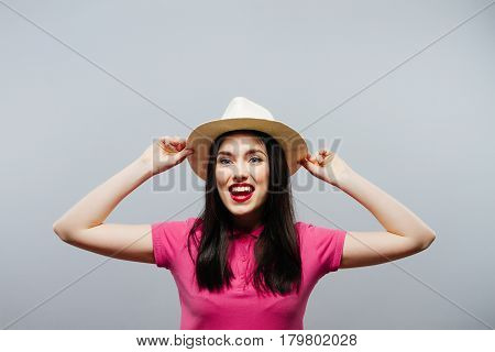 Cheerful girl holding the brim of her hat and laughing at camera in summer.