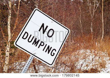 No dumping sign in natural wooded area.