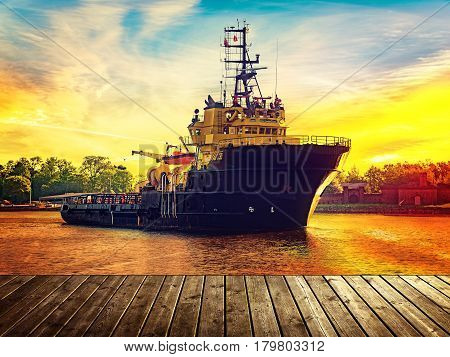 View from wooden pier with tugboat in port during sunset.