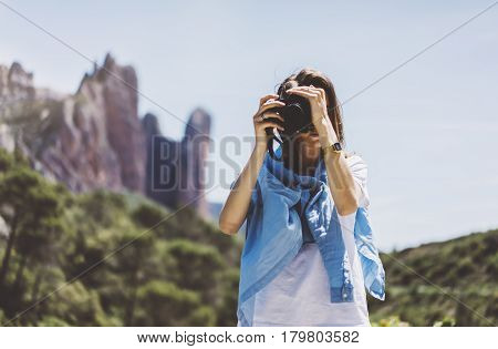Tourist traveler photographer taking pictures of amazing landscape on vintage photo camera on background valley view mockup sun flare hipster girl enjoying peak of foggy mountain nature holiday concept