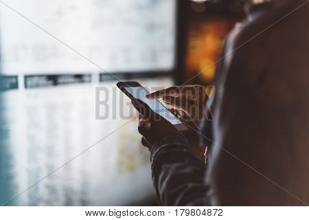 Girl pointing finger on screen smartphone on background light box in night atmospheric city map hipster using in female hands and texting mobile phone glitter street lifestyle tourist planing route