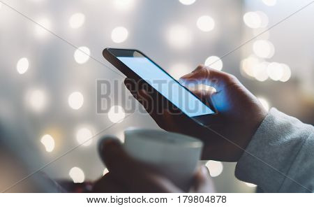 Hipster girl using mobile phone and drink coffee in home atmosphere person holding smartphone on background glow bokeh Christmas illimination female hands texting on relax glitter xmas decoration mockup blur poster