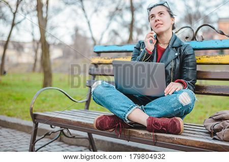 young gilr working in park on a bench with laptop